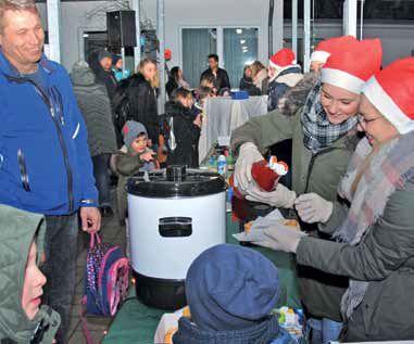 Menschen mit Nikolausmützen schenken Getränke aus