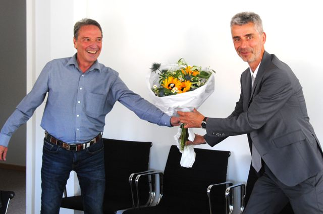 Geschäftsführer Nostadt (rechts) reicht Herrn Bast zur Verabschiedung einen Blumenstrauß