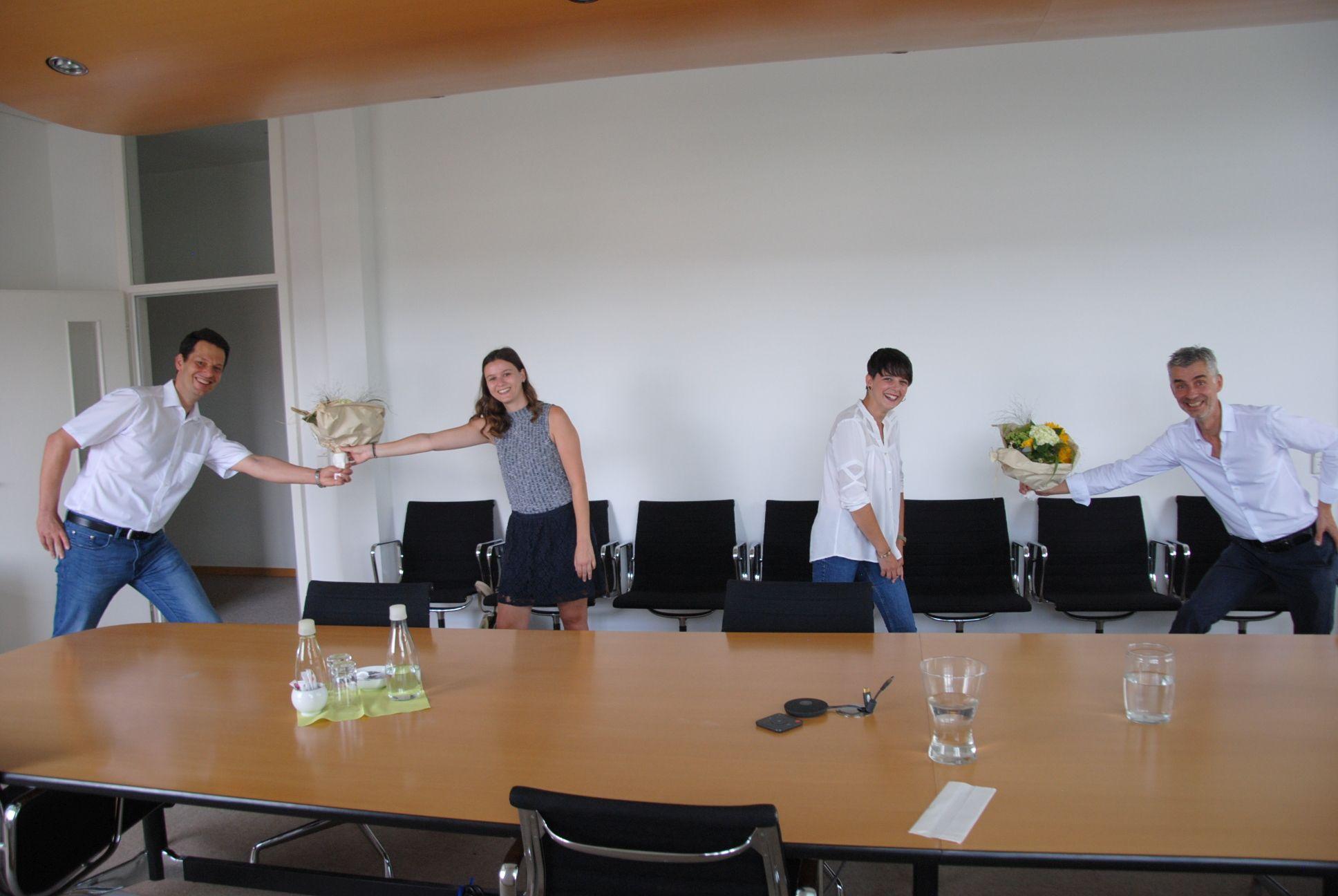 Geschäftsführer Herr Nostadt (re.) und Ausbildungsleiter Herr Mzi überreichen Blumensträuße an Frau Eller (li.) und Frau Ciccarella (re.).