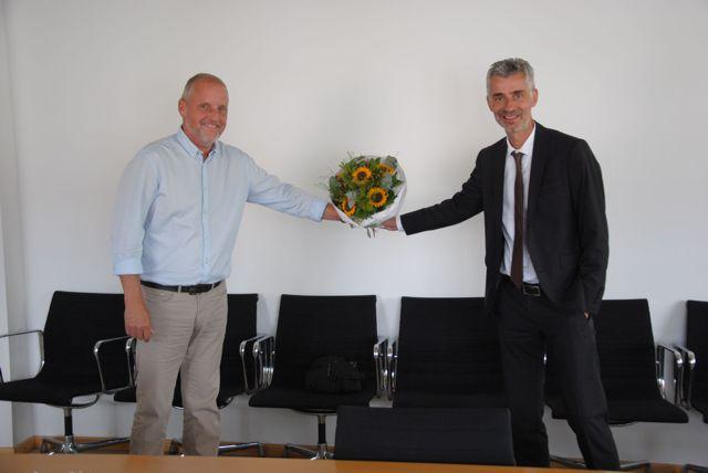 Herr Nostadt (rechts) überreicht Herrn David einen Blumenstrauß