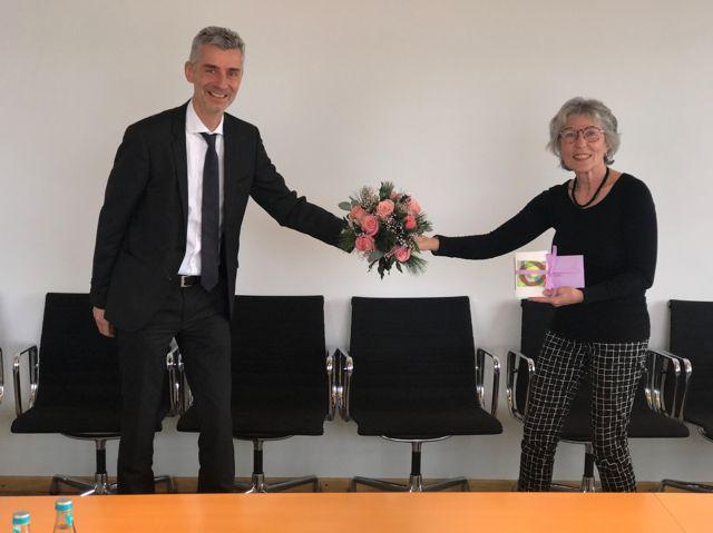 Geschäftsführer Nostadt überreicht Frau Wunderlich einen Blumenstrauß