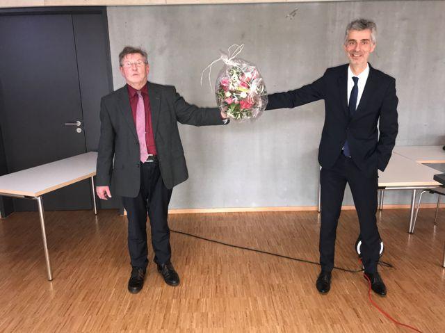 Der Geschäftsführer Herr Nostadt überreicht Herrn Karg eine Blumenstrauß