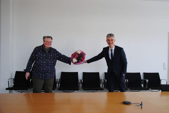 Frau Untiedt erhält von Herrn Nostadt einen Blumenstrauß
