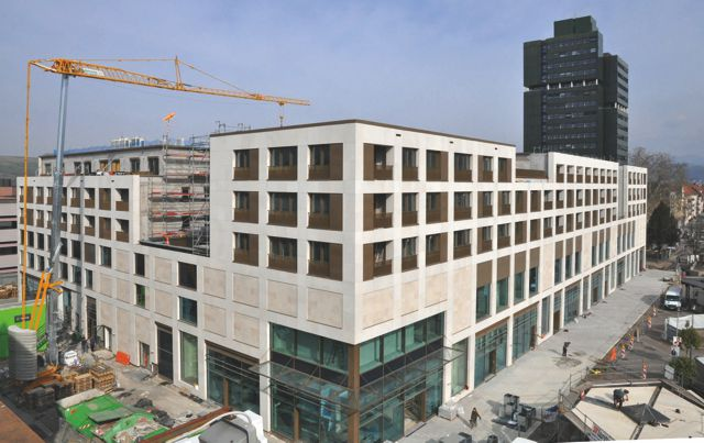 Das neue Wohn- und Geschäftshaus in Lörrach noch mit Baukran, im Hintergrund das Rathaus von Lörrach