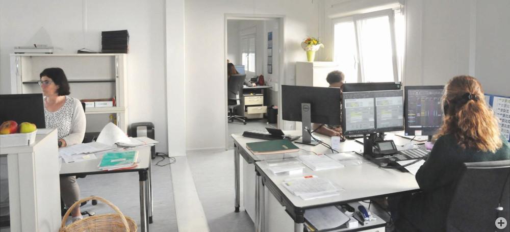 Drei Mitarbeiter/innen an den Schreibtischen im Bürocontainer