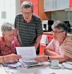 Zwei Frauen und ein Mann schauen sich Bilder an.